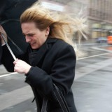 A woman fights with her umbrella as the